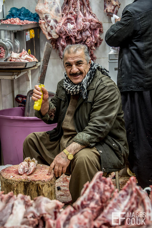 Old Man Chopping Meat At A Market In Iraq