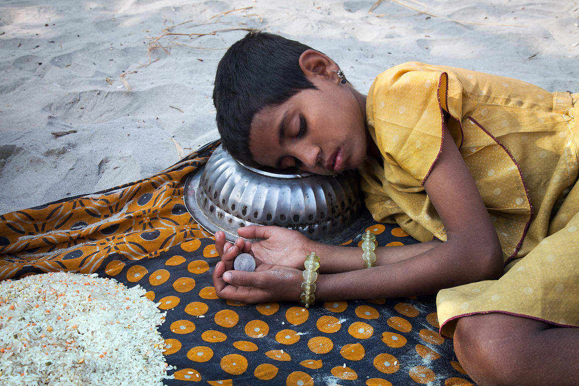 A girl falls asleep clutching a coin while panhandling for money or rice at the Gangasagar Mela, a Hindu pilgrimage to Sagar ...