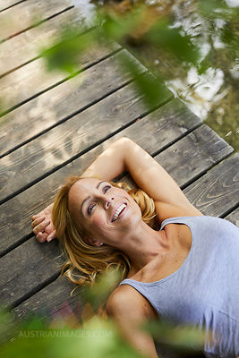 Happy blond woman lying on wooden jetty at a lake