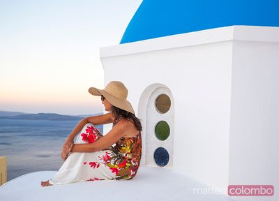 Tourist on blue domed church in Santorini, Greece
