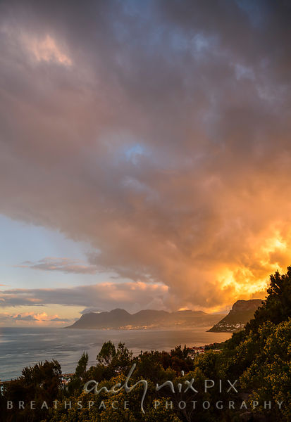 Fiery yellow clouds over mountain and sea at sunset