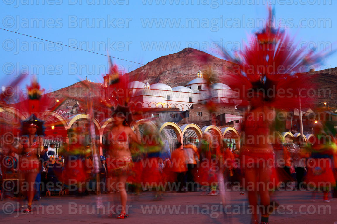 Tobas dancers at sunset, San Benito church and Cerro Rico in background, Chutillos festival, Potosí, Bolivia