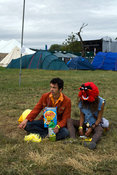 UK - Standon - A couple in costume sit in a field at the Standon Calling Festival
