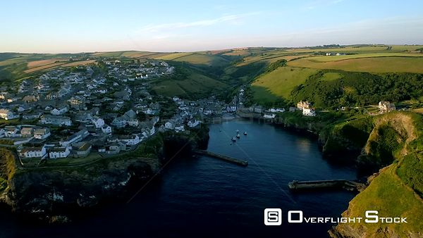 Drone flies sideways from cliffs with the village of Port Isaac behind during morning golden hour