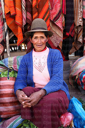 Quechua woman selling weavings in Pisac market, Sacred Valley, Cusco Region, Peru