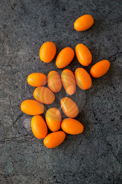 overhead group of kumquats against dark green marble background