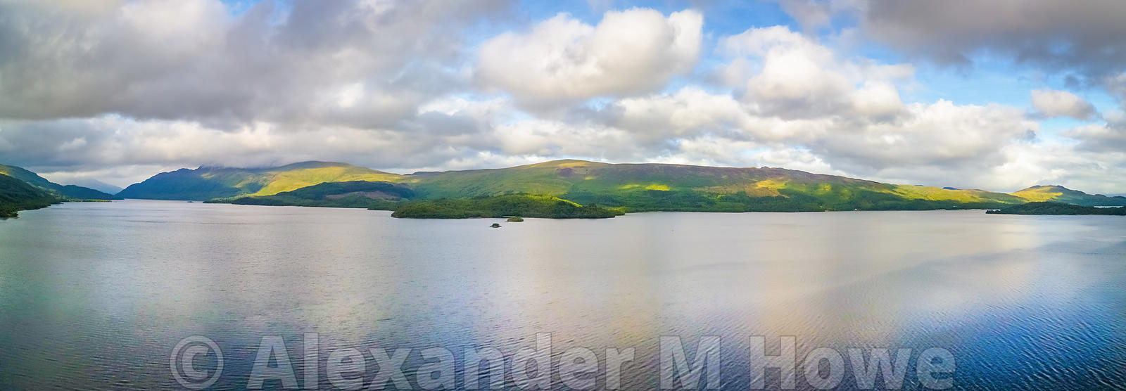 Looking across Loch Lomond towards Conic Hill with fluffy white clouds in the sky and patches of yellow sunlight on the hills...