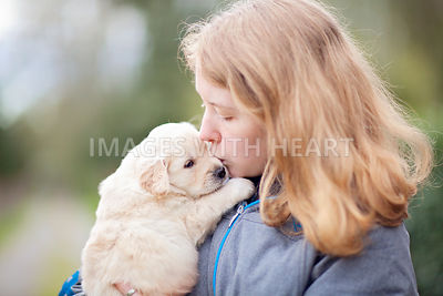 Blonde girl kissing golden retriever puppy