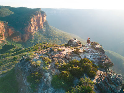 A hiker exploring the Govets Gorge of Blue Mountains, standing on a precipice with spectacular views of the sheer cliff faces...