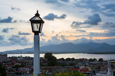 Lampadaire et vue d'ensemble de la ville de Santiago de Cuba au coucher du soleil, Cuba / Lamppost and overview of the city o...
