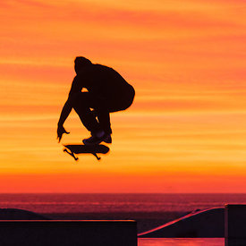 action photography of a skateboarder mid-jump at Venice Beach CA during a fiery sunset