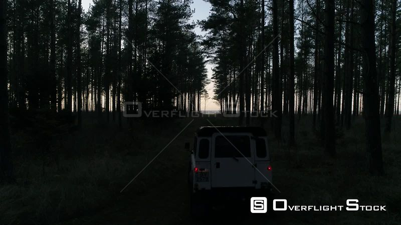 Aerial drone tracking shot of vintage 4x4 off road vehicle driving in forest towards sea at night. Latvia