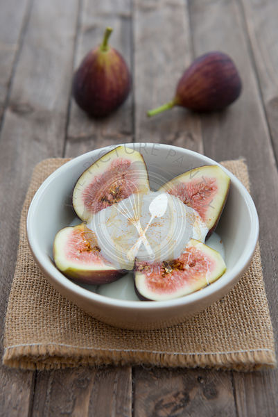 Figs in a bowl with natural yoghurt and honey on a wooden background.