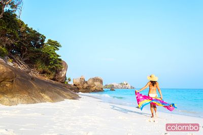 Woman with sarong on tropical beach, Thailand