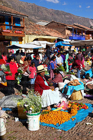 Quechua woman selling oranges in Pisac market, Sacred Valley, Cusco Region, Peru