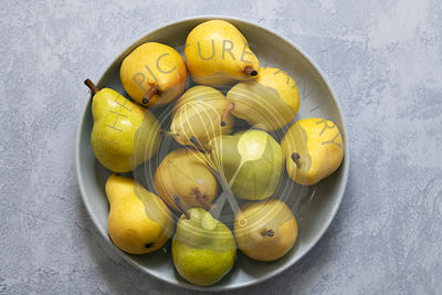 Green and yellow pears in a bowl.