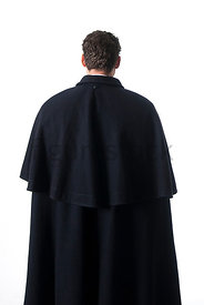 A Figurestock image of a Victorian man in a cloak, standing and looking away- shot from eye level.