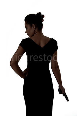 A woman standing, in silhouette, holding a gun – shot from mid level.