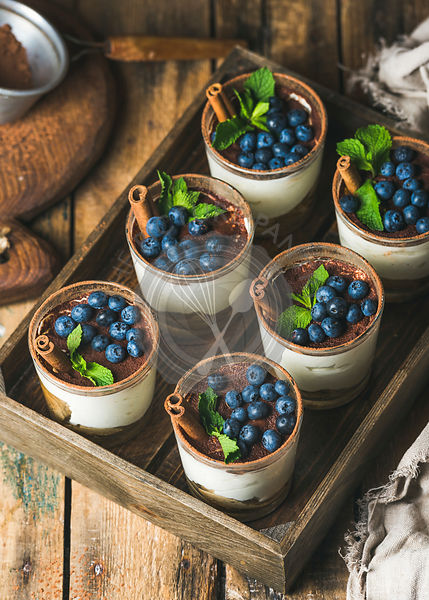 Homemade Tiramisu dessert in glasses with cinnamon, mint and fresh blueberry in wooden tray over rustic wooden background