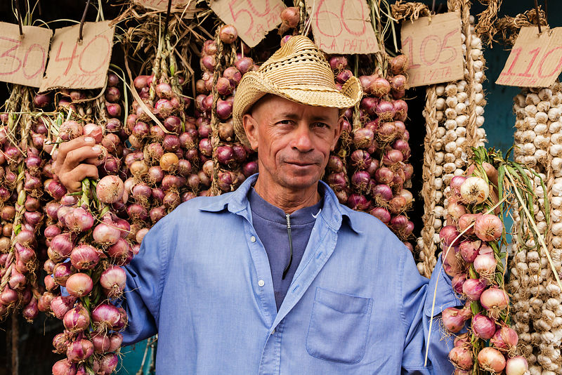 Market Seller Holding Strings of Onions