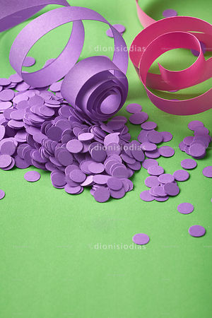 Carnival background with purple confetti and serpentines on green background