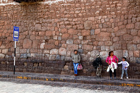 People waiting at bus stop in front of Inca stone wall, Plaza San Pedro , Cusco , Peru