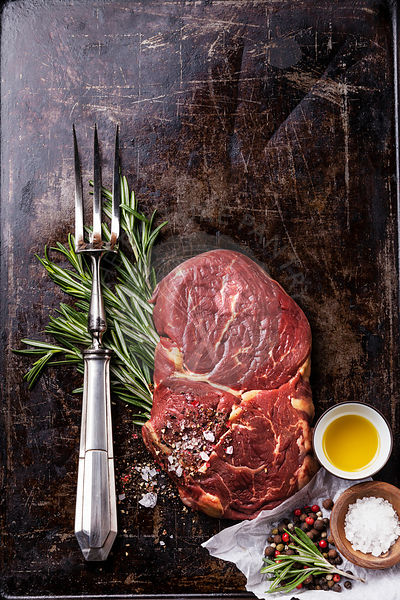 Raw fresh meat Ribeye Steak, seasoning and meat fork on dark background