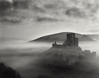 A mystical and magical dawn scene in deepest Dorset. The warm early sun radiates though the holes in the ruined battlements t...