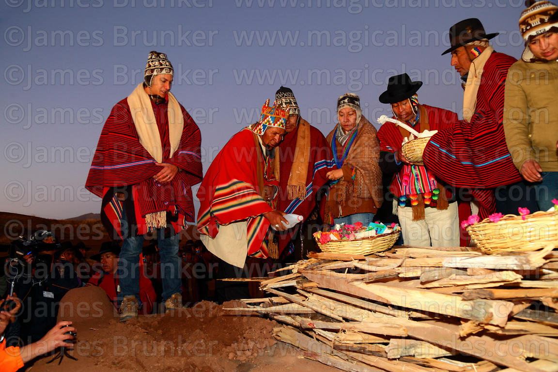 Aymara shaman or amauta pouring alcohol on firewood at start of Aymara New Year celebrations, Tiwanaku, Bolivia