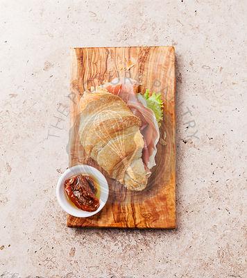 Ham croissant sandwich on stone textured background