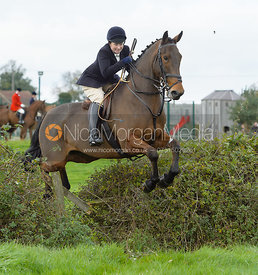 Sophie Oliver jumping a hedge near the meet in Long Clawson