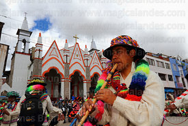Musician playing quena flute in front of Sanctuary of Virgen de la Candelaria, Puno, Peru