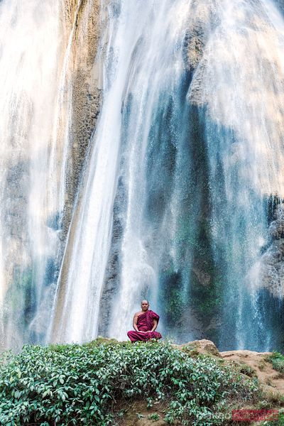 Buddhist monk meditating under big waterfall, Burma