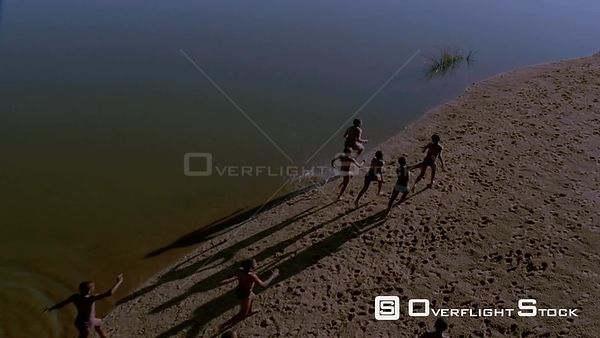 Top shot, slow motion rear view of boys running along beach with water in background