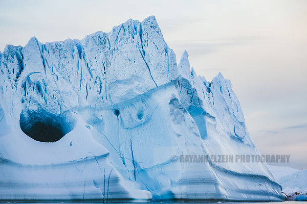 Extremely large iceberg with a big cave on its flank in Ilulissat, Greenland