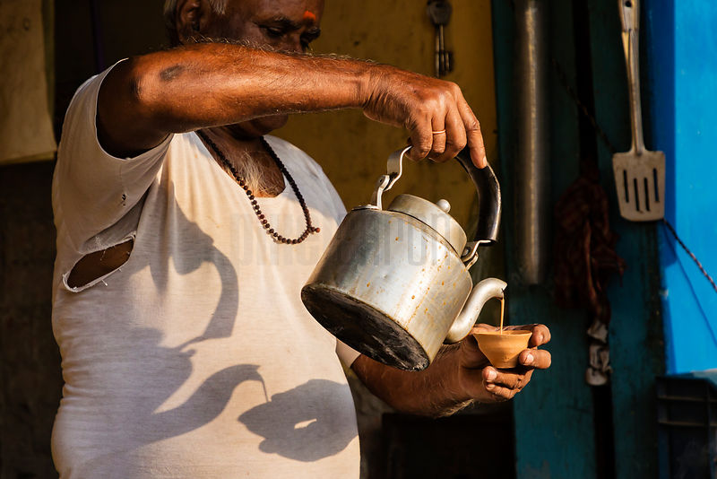 Chai Wallah Pouring a Cup of Tea at a Street Stall