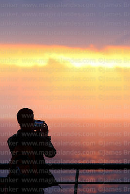 Young man using smartphone to film sunset from Larcomar, Miraflores, Lima, Peru