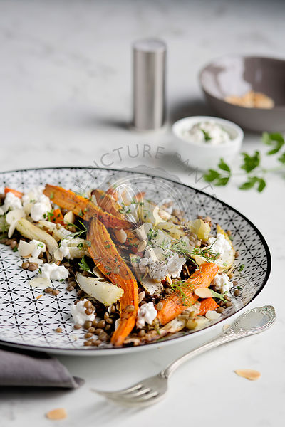 Lentil salad with roasted carrot, fennel, almonds and feta cheese on white table. Bright mood
