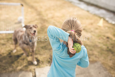 Girl Throwing Tennis Ball to Waiting Dog