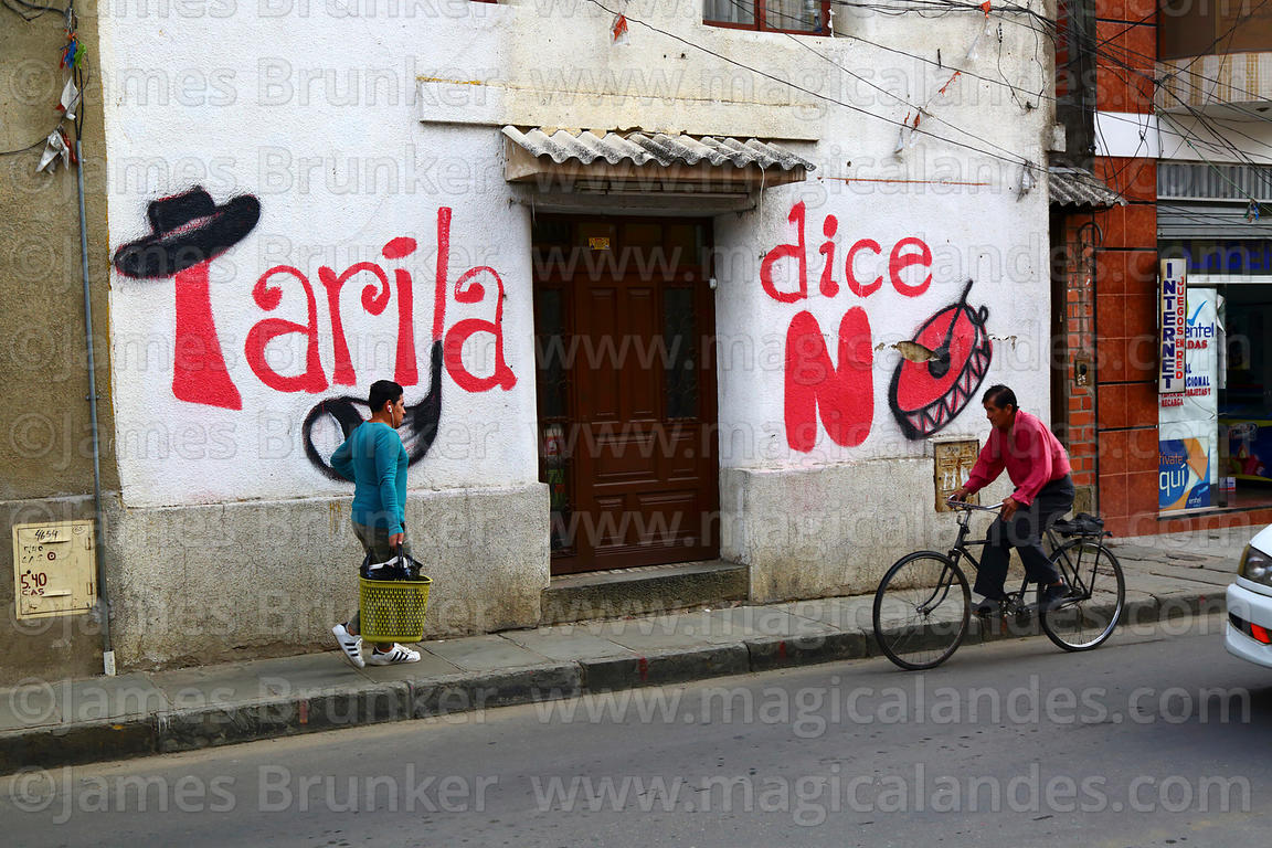 "People passing ""Tarija Says No"" political mural with cultural symbols on house, Tarija, Bolivia"