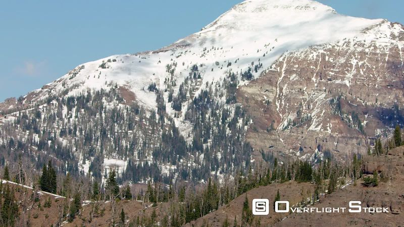 A snow-covered peak, steep cliffs and rugged terrain in the Gallatin mountain range near Yellowstone National Park