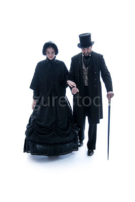 A Victorian couple walking arm in arm towards camera – shot from eye level.