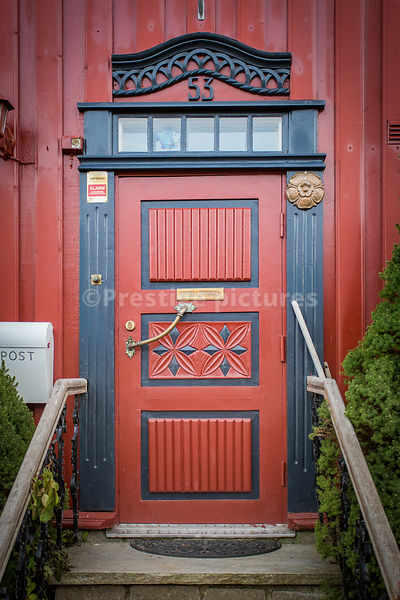Beautiful ornamented house front door with brass fittings and wooden handrails leading to it - number 53
