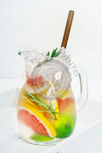 Refreshing summer homemade flavoured water cocktail with lemon, lime, orange, grapefruit and rosemary