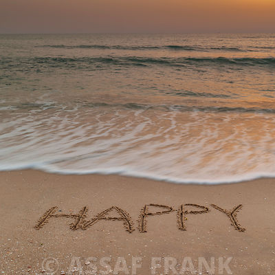 Sand writing - Word Happy written on beach