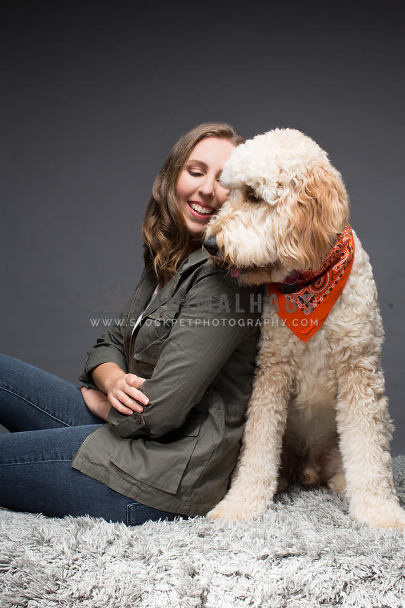 Caucasian woman nuzzling with her dog in a studio portrait.