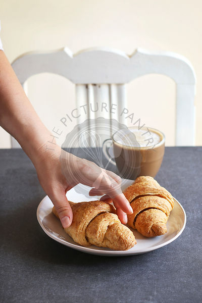 Classic breakfast with croissants and coffee.Woman holding a croissant