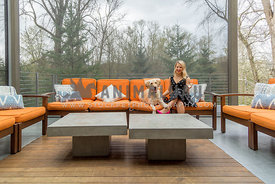 Blonde woman in polka dot dress sitting with Golden Laborador on outdoor orange sofa
