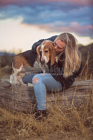 a basset hound gets a kiss from a blonde girl