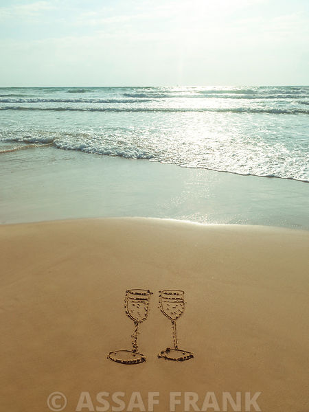 Wine glasses drawn in sand on the beach